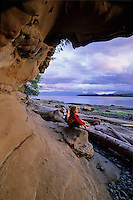 Girl, 5-7, sits under sandstone arch by Pacific Ocean, Hornby Island, BC