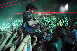 © Licensed to London News Pictures . 21/07/2013 . Suffolk , UK . Yannis Philippakis jumps in to the crowd with his guitar . Foals play at the Obelisk Arena as the closing act on the festival's main stage . The Latitude music and culture festival in Henham Park , Southwold . Photo credit : Joel Goodman/LNP