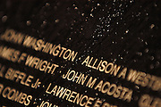 "Drops left from a passing thunder storm cling to the face of the Traveling Vietnam Veterans Memorial, the ""Traveling Wall"",  during its visit to Petoskey, Michigan."