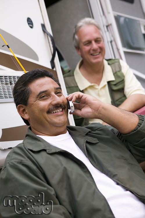 Two middle-aged man sitting beside caravan