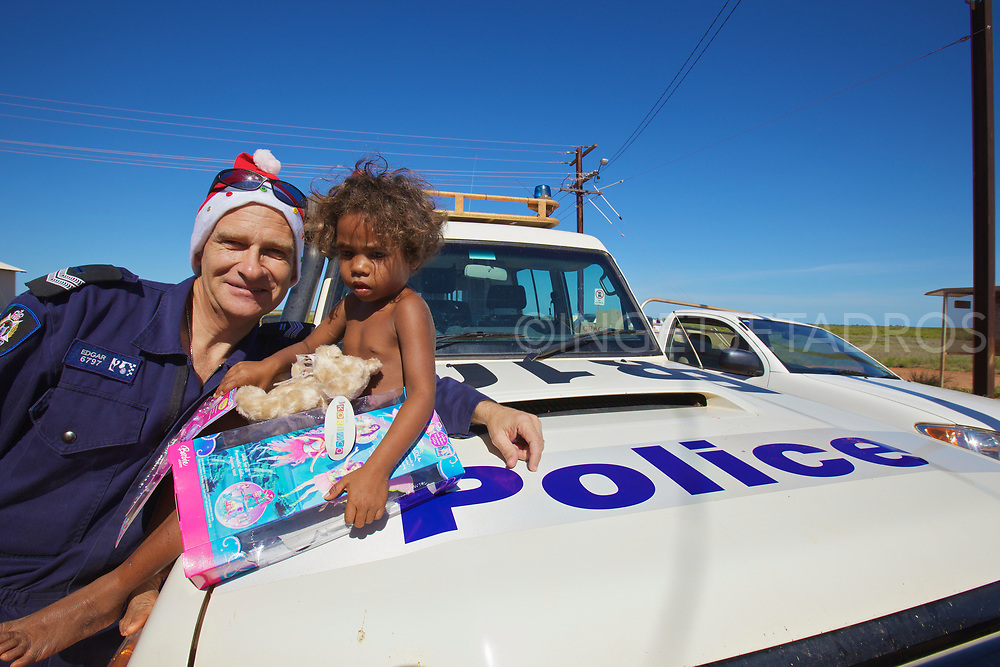 Broome policeman posing after handing out presents on Christmas morning. The Broome Police & Community Centres (PCYC) organise a present drop each year to bring festive spirit to unprivileged children of Broome, WA