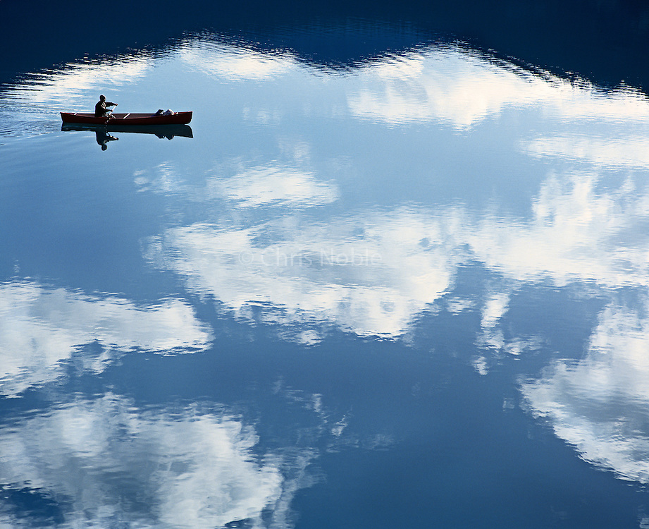 A lone canoeist paddles among reflected clouds on Emerald Lake, Yoho National Park, British Columbia Canada.