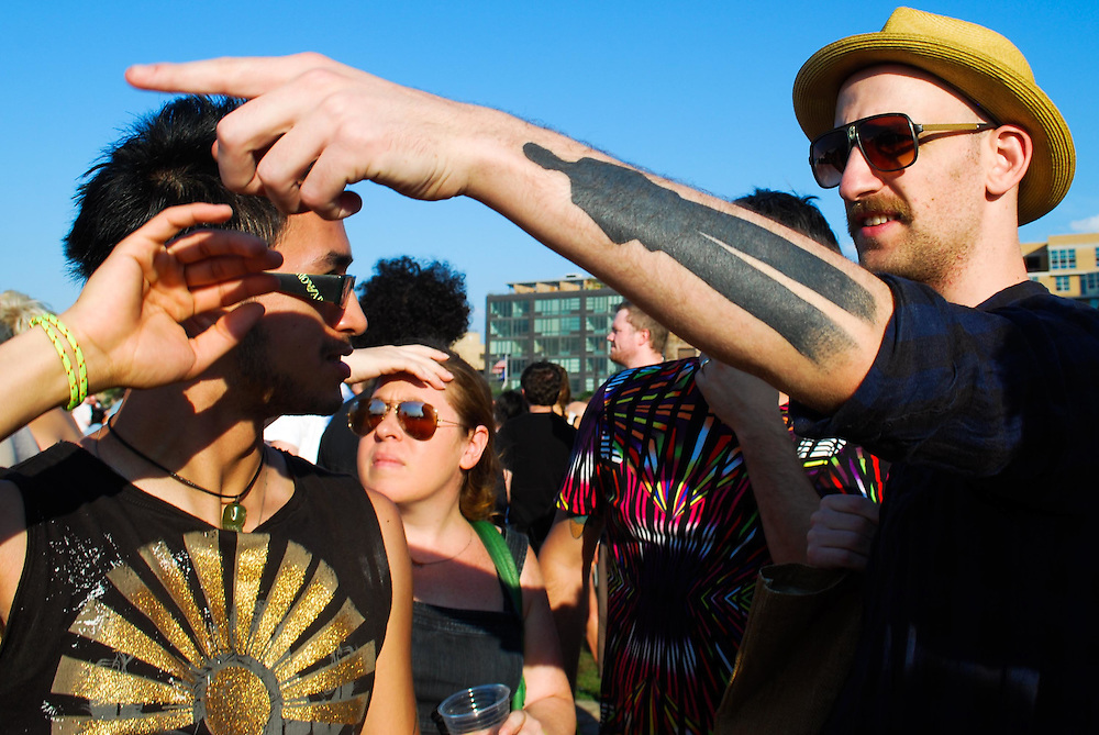 A man with a shadow tattoo points across the VIP section at the JELLY Pool Party free concert series at East River State Park, Brooklyn, New York, 2009