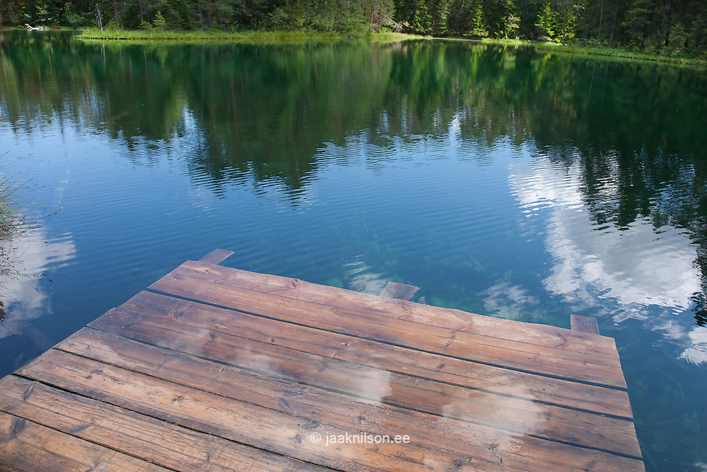 Wooden platform at green Great Äntu forest lake in Estonia. Clouds reflection on water.