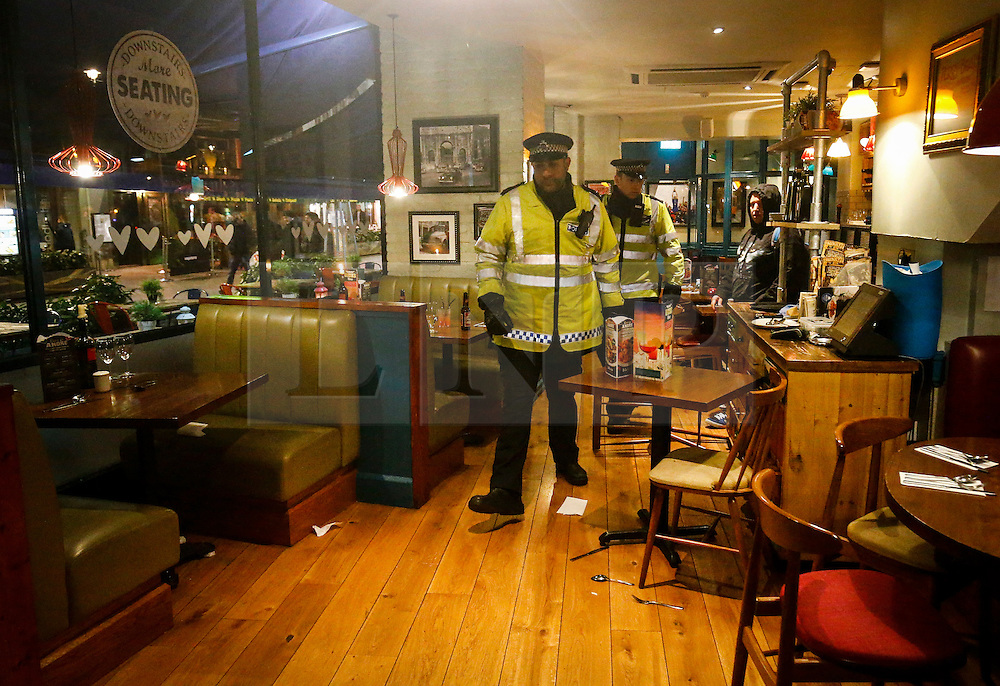 © Licensed to London News Pictures. 24/02/2016. London, UK. Signs of a disturbance can be seen as Police officers walk through Bella Italia restaurant in Leicester Square, where a man claiming to be in possession of a knife was holding a woman against her will in a hostage situation. Metropolitan Police reported the incident is not terrorist-related. Photo credit: Tolga Akmen/LNP