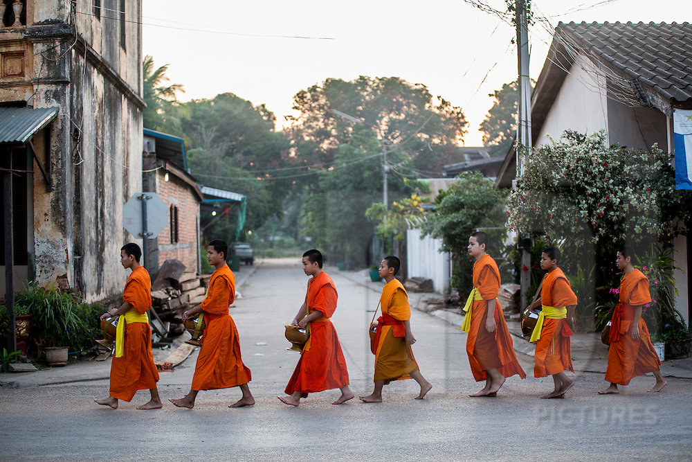 Young monks proceed through Thakhek during morning alms in Laos, Southeast Asia