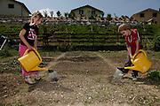 Enfants en train d'arroser leur jardin. Kinder mit Giesskanne im Gemüsegarten. Enney, Juni 2010. © Romano P. Riedo