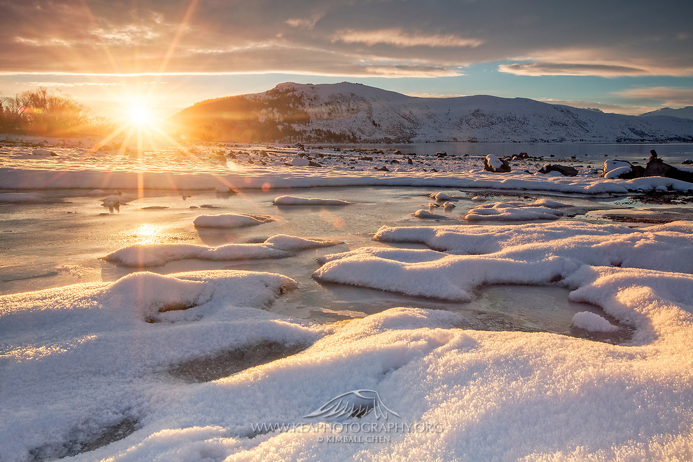 The setting sun casts a warm glow onto patches of snow along the banks of Lake Tekapo