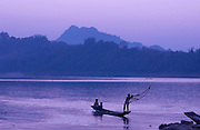 Boys fishing with a net from a boat on the Mekong River at sunset in Luang Prabang, Laos.