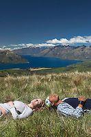 Man and woman lying in field overlooking hills and lakes