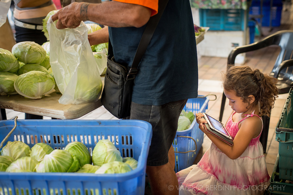 A young girl watches a video on a tabletnext to her parents vegetable stall in the municipal market of Tahiti.