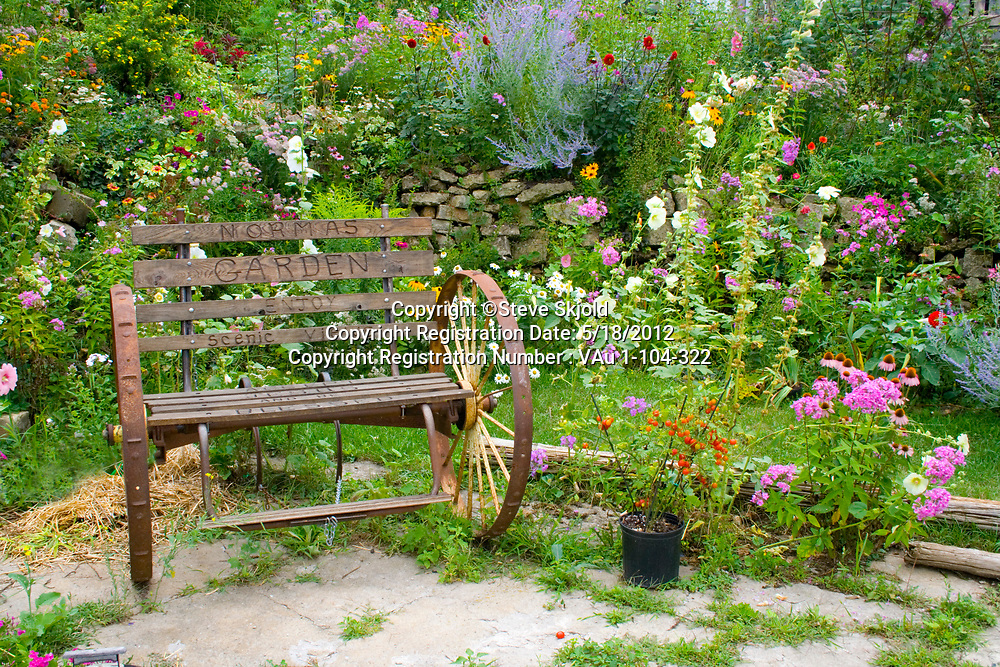 Norma's flower garden with antique spoked wheel bench. Lanesboro Minnesota MN USA