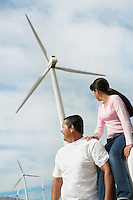 Father and daughter (7-9) near wind turbines at wind farm