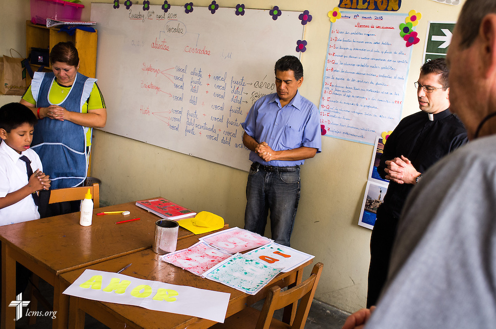 The Rev. Ross Johnson, LCMS director of Disaster Response (second from right) leads a small group in prayer at the Noe school (Spanish for Noah) near Lima, Peru, on Tuesday, April 7, 2015. The school was affected by recent landslides when heavy rains unleashed avalanches of mud and rock onto surrounding regions of neighborhoods and businesses.  LCMS Communications/Erik M. Lunsford