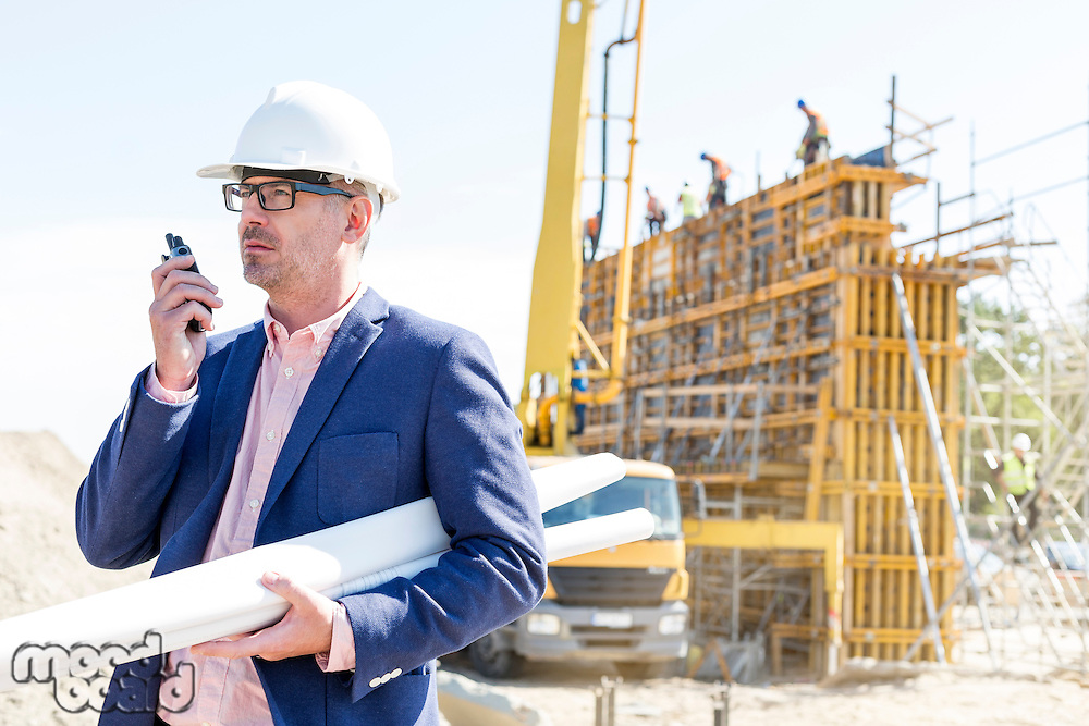 Architect using walkie-talkie while holding blueprints at construction site