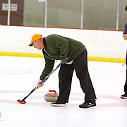 Rick Crowell, right watches Shep Sheppard sweep a stone during a curling match at the Wilmington Ice House. (Jason A. Frizzelle)