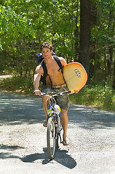 Young man with various beach sports equipment riding his bike along a wooded gravel road