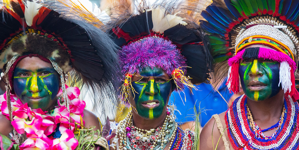 Group of women with their faces painted green and yellow. They are wearing elaborate tribal headdresses made with bird's feathers as well as ornamental necklaces for  the Goroka Show in Papua New Guinea.
