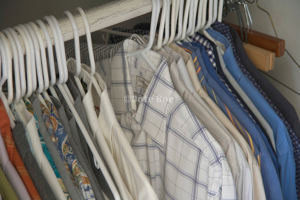 men shirts hanging in a closet
