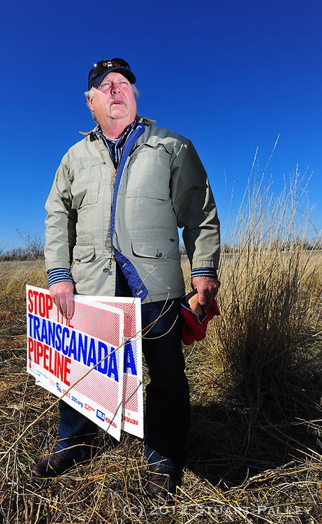 "Tom Genung of Hastings, NE poses in front of the South Branch of the Platte River. Genung is an adrent opponent of Trans Canada's failed bid to build the Keystone XL Pipeline across the Nebraska Sandhills and Ogalalla Aquifier. He is part of an informal group he calls the ""Sheriff's Posse"" and testified in front of Nebraska's Unicameral Legislature against the Keystone Pipeline construction. Genung and his fellow Nebraskans have been successful in stopping the bid for the time being, but still face efforts from Trans Canada to expand capacity to pump hot tar sands from Alberta, Canada South to oil refiniders in Houston and the Gulf Coast area."