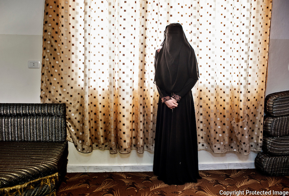 Layla, 15, stands alone in the niqab she recently started wearing. Her 17 year old sister has just married, leaving her alone in the house with her widowed mother and four siblings. The marriage proposals are already coming to her. She had dreamt of finishing high school and becoming a teacher. She says that while early marriage was common in Deraa, at least girls were allowed by their families to walk freely in their community and go to school. Here, she feels she is slowly dying indoors, day in and day out. 2014