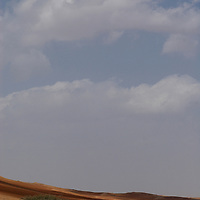 """Oman, Wahiba Sands. January/25/2008...One of the flat, hard-packed corridors that separates dune from dune in the Wahiba Sands. """"We rest for an hour and give the sun a chance to move over in the direction of clouds that have appeared on the horizon""""."""