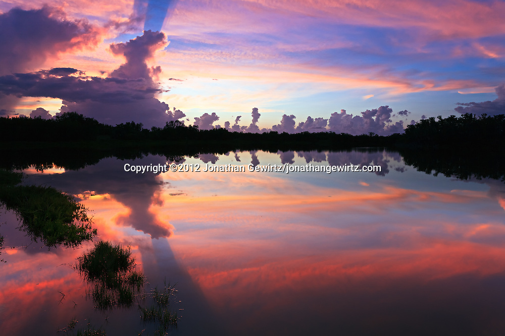 The colorful red skies of a rainy-season sunset reflect off the surface of Eco Pond in the Flamingo section of Everglades National Park, Florida. WATERMARKS WILL NOT APPEAR ON PRINTS OR LICENSED IMAGES.