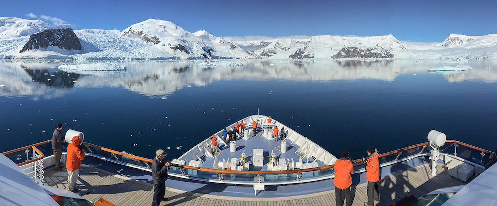 Bow of the ship POV entering refelcting glaciers and mountains near Cuverville Island, Antarctica.