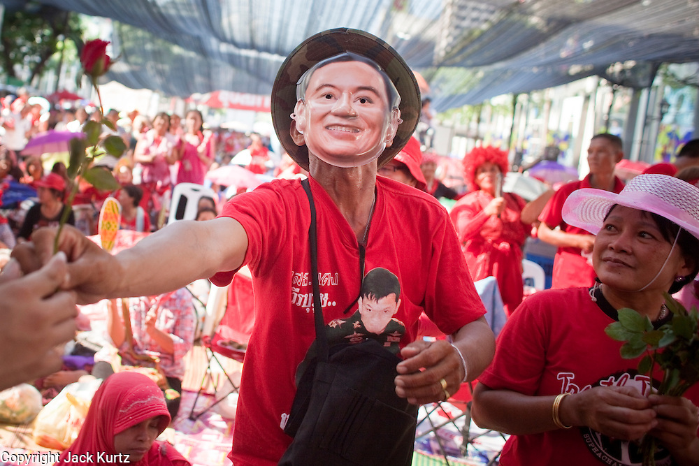"09 MAY 2010 - BANGKOK, THAILAND: A Red Shirt protesters wearing a Thaksin Shinawatra mask hands a flower to an entertainer at the Red Shirt rally in Bangkok Sunday. The Red Shirt leaders said Sunday they still conditionally supported the Prime Minister's ""Road Map to Reconciliation"" but that their opponents the Yellow Shirts needed to sign on to make the five point ""Road Map"" viable. About 5,000 people mostly from northeast Thailand, joined the Red Shirts in Ratchaprasong over the weekend. Members of the United Front of Democracy Against Dictatorship (UDD), also known as the ""Red Shirts"" and their supporters have occupied Ratchaprasong intersection, the site of Bangkok's fanciest shopping malls and several 5 star hotels, since April 4. The Red Shirts are demanding the resignation of current Thai Prime Minister Abhisit Vejjajiva and his government. The protest is a continuation of protests the Red Shirts have been holding across Thailand. They support former Prime Minister Thaksin Shinawatra, who was deposed in a coup in 2006 and went into exile rather than go to prison after being convicted on corruption charges. Thaksin is still enormously popular in rural Thailand.   PHOTO BY JACK KURTZ"