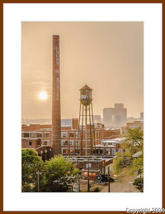 Sunset over Richmond, Virginia from Libby Hill on a hazy, smokey afternoon in May. The Lucky Strike smoke stack and an old water tower rise above Shockoe Bottom.