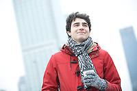 Smiling man in warm clothing looking away while holding disposable cup outdoors