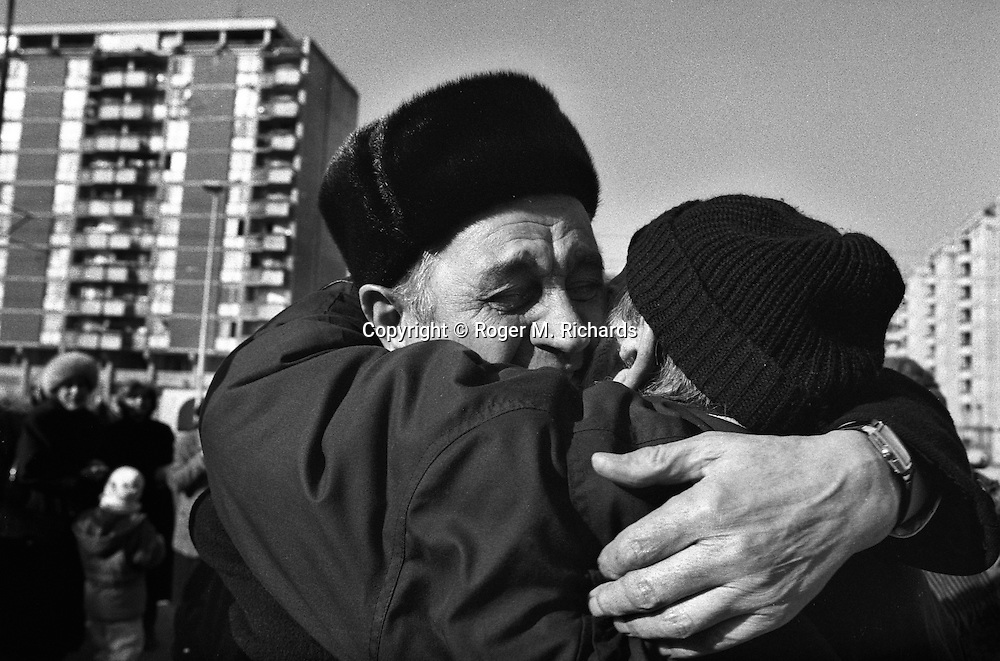 Two friends, a Serb and a Muslim, greet each other after four years of separation on the Serb-side of the Bratstvo i Jedinstvo Most (Brotherhood and Unity bridge) during the final days of the siege of the city, Sarajevo, Bosnia and Herzegovina, February 1996. PHOTO BY ROGER RICHARDS