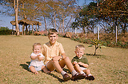 An older uncle with his two nephews sit on tropical grass in the family African garden in 1970.