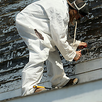 Vernon Brown, an employee with Mask Construction Services out of Tupelo, work on scraping off the old lead base paint from the Spain home as they prep it for new paint on Friday in Tupelo.