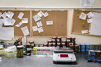 """PISCIOTTA, ITALY - 22 APRIL 2018: Daily orders, products and a scale are seen here in the """"Alici di Menaica"""" processing workshop, owned by Donatella Marino and her husband Vittorio Rimbaldo, in Pisciotta, Italy, on April 22nd 2018.<br /> <br /> Former restaurant owners Donatella Marino and her husband Vittorio Rimbaldo have spent the recent years preparing and selling salted anchovies, called alici di menaica, to a growing market thanks to a boost in visibility from the non-profit Slow Food.  The ancient Menaica technique is named after the nets they use brought by the Greeks wherever they settled in the Mediterranean. Their process epitomizes the concept of slow food, and involves a nightly excursion with the special, loose nets that are built to catch only the larger swimmers. The fresh, red anchovies are immediately cleaned and brined seaside, then placed in terracotta pots in between layers of salt, to rest for three months before they're aged to perfection.While modern law requires them to use PVC containers for preserving, the government recently granted them permission to use up to 10 chestnut wood barrels for salting in the traditional manner. The barrels are """"washed"""" in the sea for 2-3 days before they're packed with anchovies and sea salt and set aside to cure for 90 days. The alici are then sold in round terracotta containers, evoking the traditional vessels that families once used to preserve their personal supply.<br /> <br /> Unlike conventional nets with holes of about one centimeter, the menaica, with holes of about one and half centimeters, lets smaller anchovies easily swim through. The point may be to concentrate on bigger specimens, but the net also prevents overfishing."""