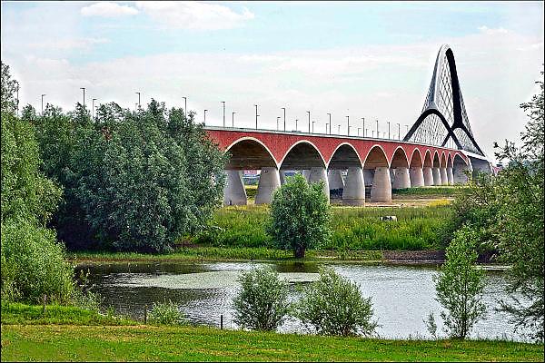 Nederland, Nijmegen, 2506-2015 De stadsbrug van de stad Nijmegen, de Oversteek en de uiterwaarden van de Waal. Gebouwd door de aannemers BAM Civiel B.V. en Max Bogl Nederland B.V. De brug is vernoemd naar de heldhaftige oversteek van de rivier de Waal die Amerikaanse soldaten op dit punt maakten tijdens de operatie Market Garden in de tweede wereldoorlog om met succes de oude Waalbrug te veroveren. De overspanning is een belangrijke schakel in de ontlasting van de stad van het doorgaande verkeer. De Oversteek is een boogbrug van 285 meter lang en 60 meter hoog en is de op een na langste hoofd overspanning van Nederland, en de grootste boogbrug van Europa met een enkelvoudige boog. De nieuwe oeververbinding moet zorgen voor een betere spreiding en doorstroming van verkeer binnen de stad Nijmegen. Na 75 jaar is er eindelijk een tweede vaste verbinding voor de stad. De skyline van de stad is veranderd. De brug is een ontwerp van de Belgische architecten Ney en Paulissen.Bridge the Crossing, named after the heroic crossing of the river Waal in 1944 by american paratroopers . WW2 Foto: Flip Franssen/Hollandse Hoogte