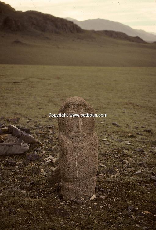 Mongolia. stone statue (Turkish 6th century)                / Alignement de statues monolithes anthropomorphes. (Granit, VI-VIIIème siècle). / Ces statues représentent des  - 'idoles de pierre -  (KUN TCHULUU), typiques de l'art monumental des steppes d'Asie Centrale. D'après la coutume du culte des Ancêtres, ce genre de statue était érigée à la surface d'une tombe d'un noble guerrier, à l'époque des Turcs Célestes. Leur visage présente pratiquement toujours les mêmes caractéristiques : faciès plat, pommettes saillantes, yeux en amandes et moustache. L'idole, vêtue d'une robe avec ceinture, a le bras droit plié au niveau du coude et tient une coupe. Parfois, des oiseaux de passage viennent s'y poser. (Sum de DJARGALAN, dans l'aymag de GOV ALTAY  / /9    L0006223  /  P0002614