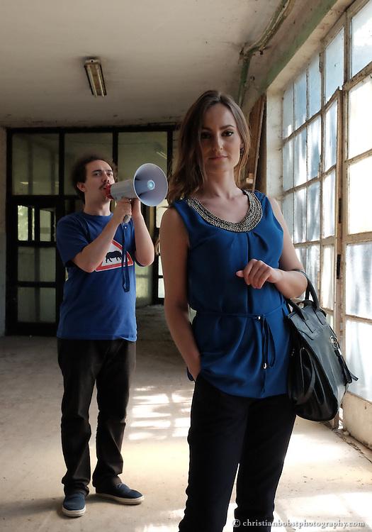 Merfida Jerliu, Teilnehmerin der TV-Sendung PunPun und Visar Arifay, Mitinhaber der Grafikagentur Trembelat in Pristina, der im Auftrag von Helvetas die TV-Sendung PunPun entwickelt und moderiert hat. In diesem Bild auf dem stillgelegten Fabrikareal, auf welchem das Studio der Show Pun Pun aufgebaut war. Das Megafon diente in der Sendung dazu, die Teilnehmer anzuspornen. Gleichzeitig symbolisiert es die Kommunikation mit einem grossen Publikum.