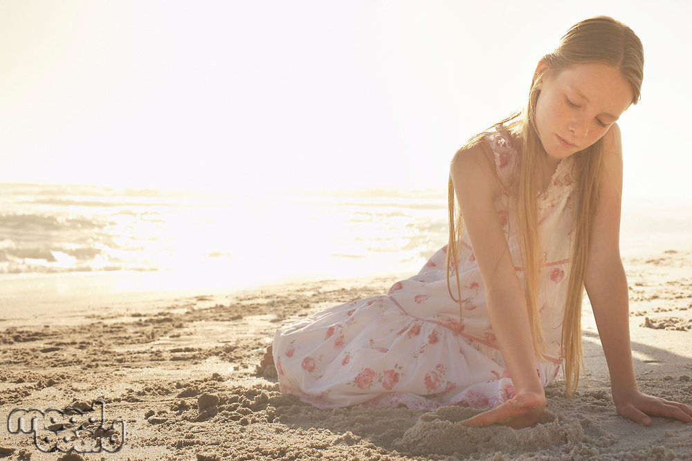 Girl (10-12) playing in sand on beach at sunset