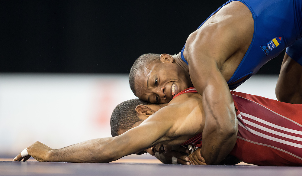 Andres Montano (top) of Ecuador tries to get position on Jansel Ramirez of the Dominican Republic in their quarter final bout in the 59kg class of the men's greco-roman wrestling  at the 2015 Pan American Games in Toronto, Canada, July 15,  2015.  AFP PHOTO/GEOFF ROBINS