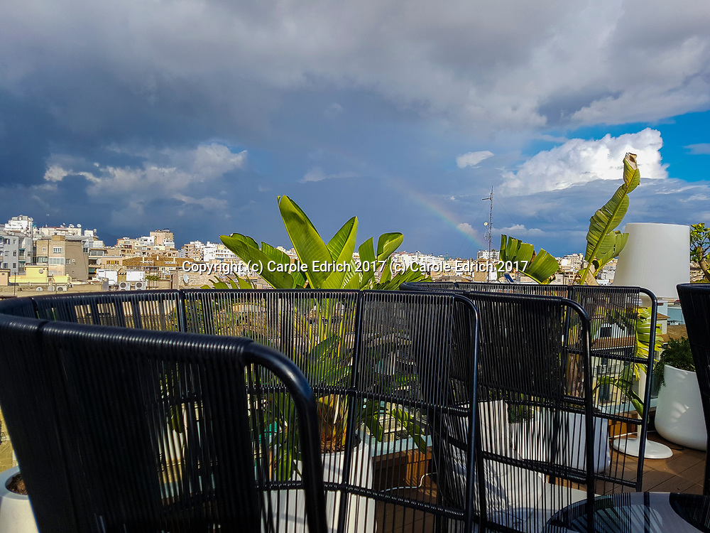 Rainbow in distance seen behind stylish chairs at Nakar Hotel rooftop bar. (C) Carole Edrich 2017