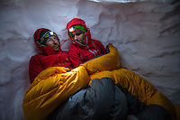 Two male mountaineers covered with a sleeping bag in an improvised snow cave on Glacier Blanche, Chamonix, France.