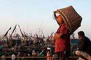 A boy waits on the dock with his basket ready to receive the days catch from fishermen in Chittagong, Bangladesh.