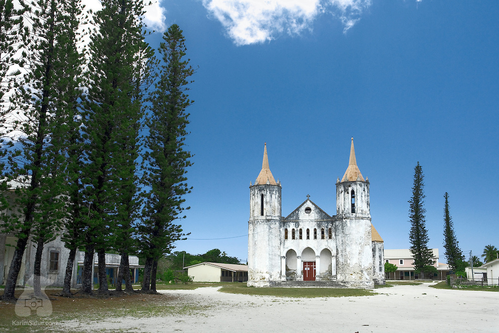 An old church stands next to tall 'colonial pines' near Fayaoue, Ouvea island, New Caledonia. Ouvea lies rooughly 100Km off the Caledonian mainland and is part of the Loyalty island group. During the missionary fervor of the 19th century, many churches were built on the island. The London Missionary Society and the French Marist Mission were the main actors in the theater staging fierce 'battles' of ideology, religion and influence between catholic and protestant missionaries.