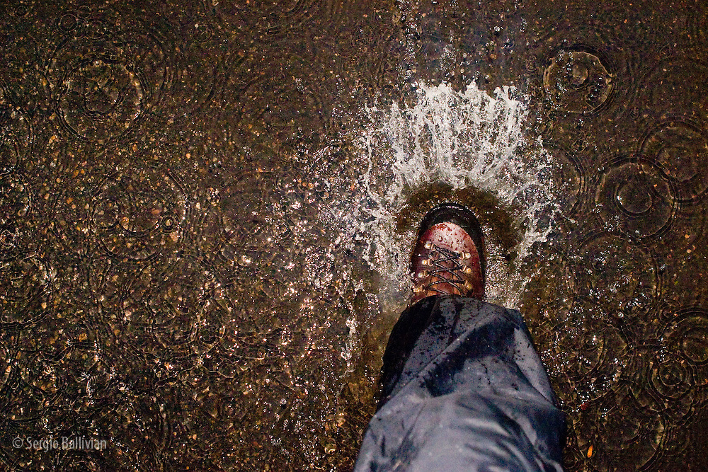 A hiking boot splashing in a puddle in a parking lot in Boulder, CO