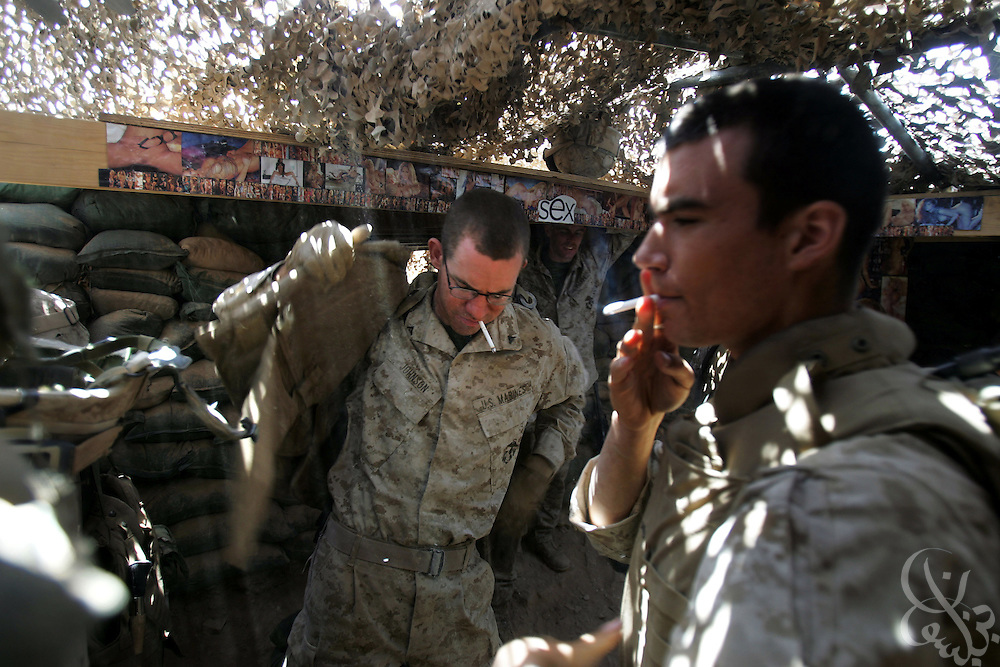 U.S. Regimental Combat Team 2 Marines smoke cigarettes during a change of shift in a remote fortified bunker position at a radio communication tower May 18, 2005 just outside the Iraqi city of Al-Qaim near the Syrian border.