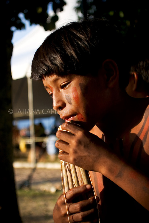 A Manoki (Irantxe) boy playing a traditional flute that is part of their initiation, when the boys are from 12 to 14 years old.