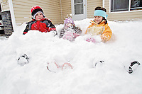 Tucker Booth, 4, left, his sister, Katie Jo Booth, 6, and friend Torie Bradley, 7, get buried in the snow of the Booth's front yard in Coeur d'Alene as they try to make the most of their snow day off from school Friday.