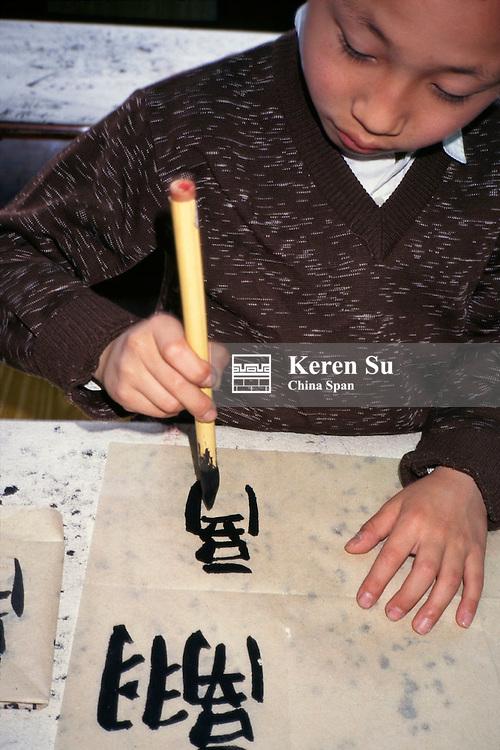 Boy practicing calligraphy with brush, Shanghai, China