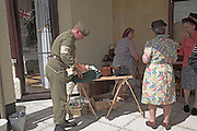 Nineteen forties Living Histroy event. Home Guard soldiers and women having a chat and tea break.
